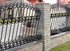 Комбинированный кованый забор с кирпичными столбами